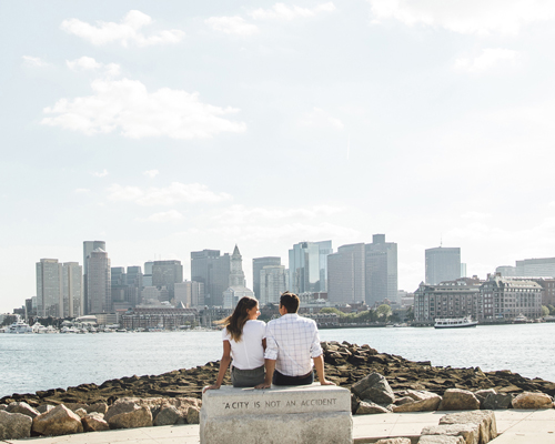 Couple by the waterside with city views